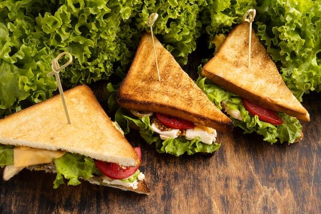 Hoge hoek van driehoeksandwiches met salade en tomaten