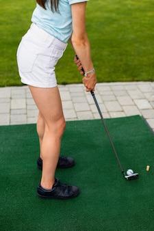 Hoge hoek van een golfspeler oefenen