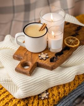Hoge hoek van een kopje koffie met kaarsen en kaneelstokjes