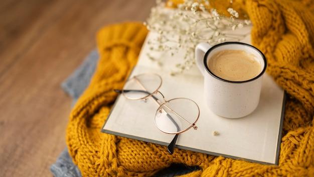 Hoge hoek van een kopje koffie op boek met glazen en truien
