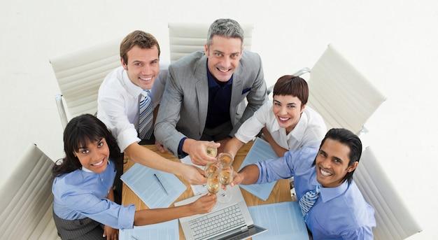 Hoge hoek van een succesvol commercieel team dat met champagne roostert