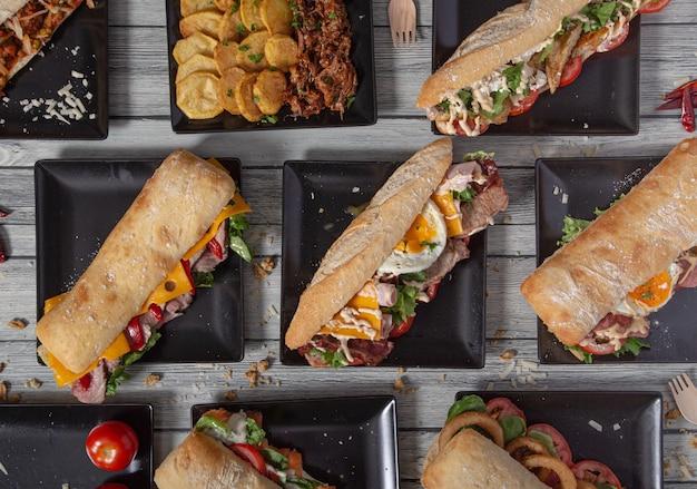 Hoge hoek van een verscheidenheid aan heerlijke sandwiches met een verscheidenheid aan ingrediënten op een houten tafel.