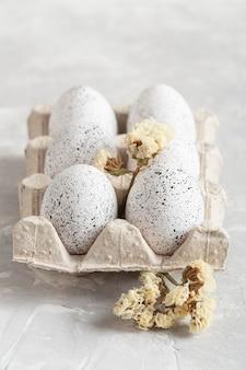 Hoge hoek van eieren voor pasen in doos met bloemen