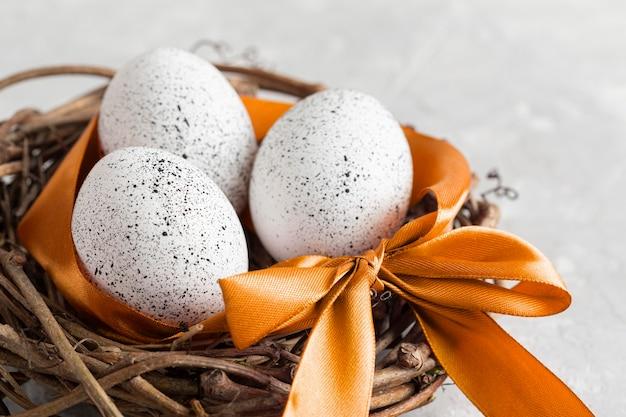 Hoge hoek van eieren voor pasen in vogelnest met lint en boog