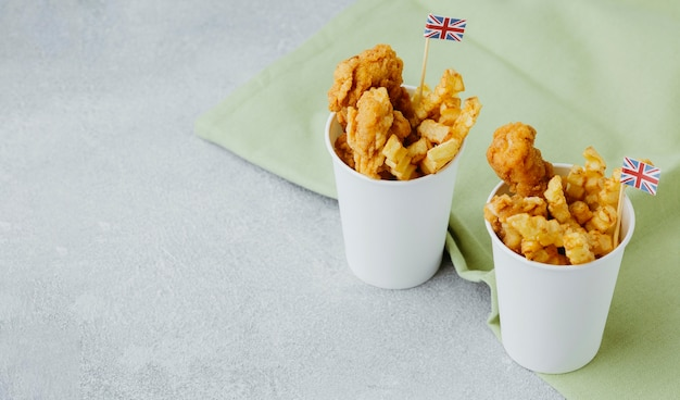 Hoge hoek van fish and chips in papieren bekers met vlaggen van groot-brittannië en kopieer de ruimte