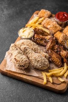 Hoge hoek van frieten met sauzen en gebakken kip
