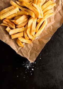 Hoge hoek van frieten op papier met zout
