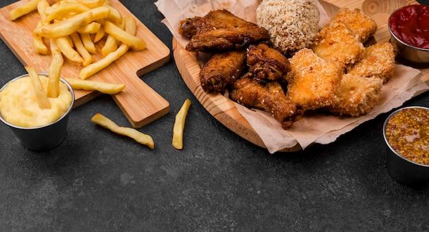 Hoge hoek van frietjes en gebakken kip
