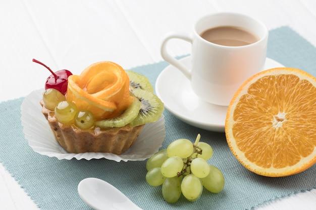 Hoge hoek van fruittaart met koffie en sinaasappel