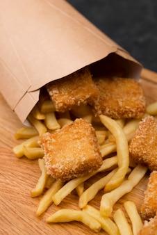 Hoge hoek van gebakken kip met frietjes en papieren zak