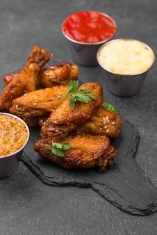 Hoge hoek van gebakken kip op leisteen met verschillende sauzen