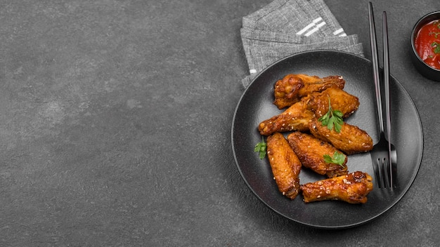 Hoge hoek van gebakken kip op plaat met saus en kopieer de ruimte