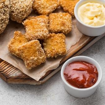 Hoge hoek van gebakken kipnuggets met twee verschillende sauzen