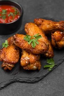 Hoge hoek van gebakken kippenvleugels op leisteen met saus
