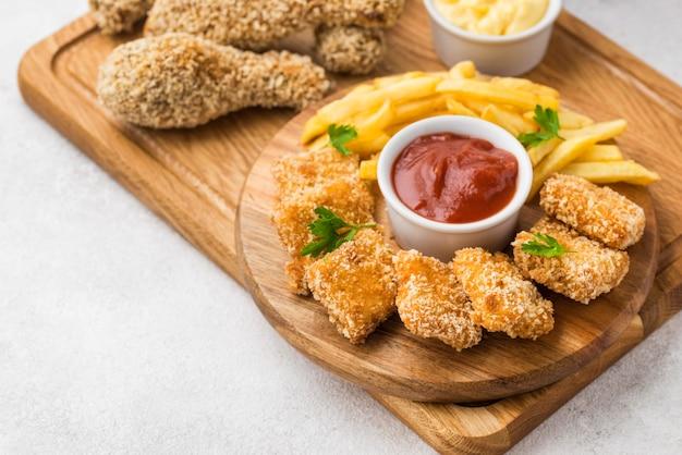 Hoge hoek van gebraden kippenpoten en nuggets met saus en exemplaarruimte