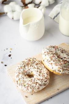 Hoge hoek van geglazuurde donuts met hagelslag en katoenbloem