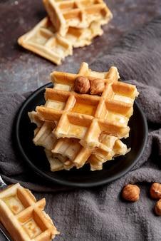 Hoge hoek van gestapelde wafels met hazelnoten en honing