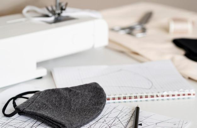 Hoge hoek van gezichtsmasker met naaimachine en notebook