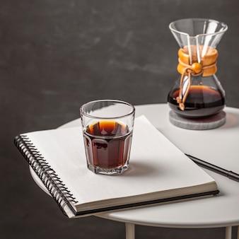 Hoge hoek van glas koffie met notitieboekje en pen