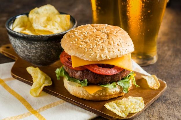 Hoge hoek van glazen bier met cheeseburger en chips