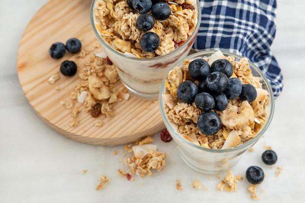 Hoge hoek van glazen met ontbijtgranen en yoghurt