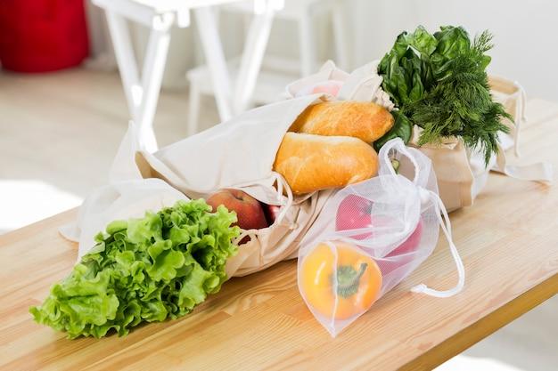 Hoge hoek van groenten en fruit op tafel met herbruikbare tassen