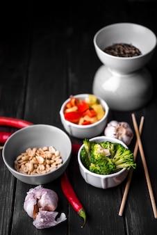 Hoge hoek van groenten in cup met pinda's en knoflook