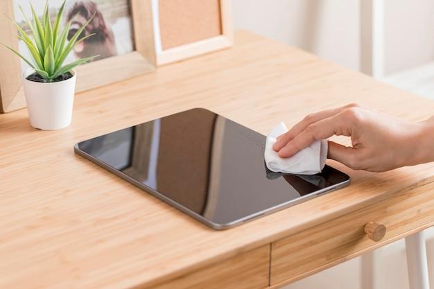 Hoge hoek van hand desinfecterende tablet op bureau