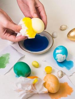 Hoge hoek van handen die ei verven voor pasen