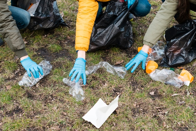 Hoge hoek van handen grijpen plastic flessen