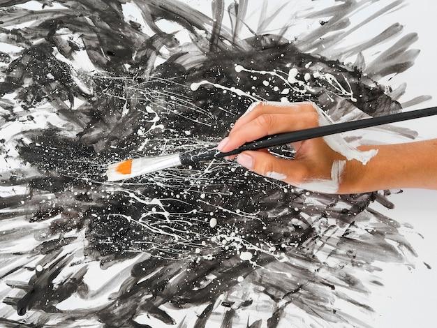 Hoge hoek van handen met borstel met verf