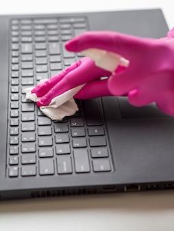Hoge hoek van handen met chirurgische handschoenen die laptop oppervlak schoonmaken
