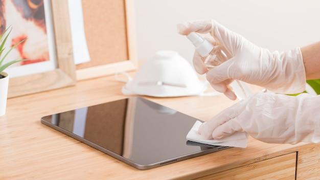 Hoge hoek van handen met chirurgische handschoenen die tablet op bureau desinfecteren