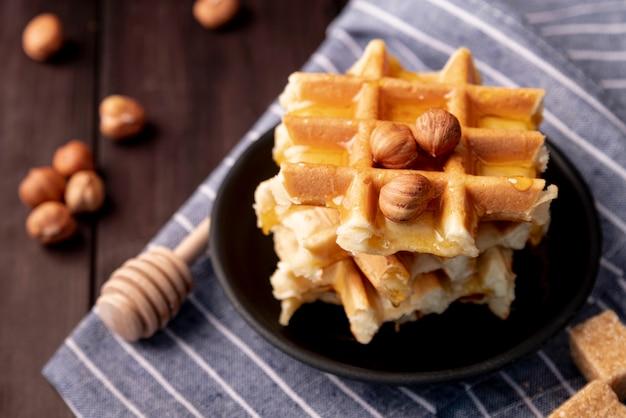 Hoge hoek van hazelnoten en honing bovenop wafels op plaat
