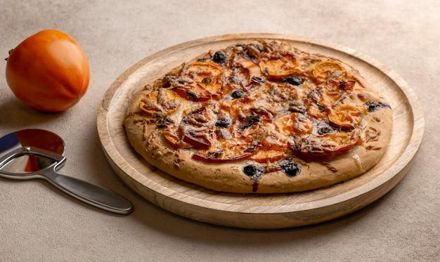 Hoge hoek van heerlijke pizza met persimmon