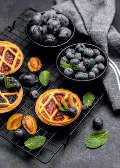 Hoge hoek van heerlijke taarten met pruimen op koelrek