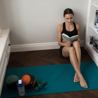 Hoge hoek van het sportieve boek van de vrouwenlezing met geneeskundebal en gewichten naast haar