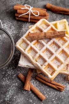 Hoge hoek van kaneelstokjes op suiker gepoederde wafels
