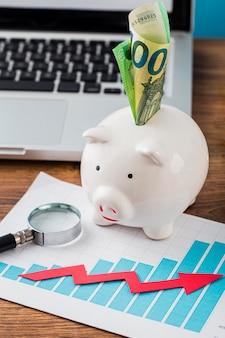 Hoge hoek van kantoorartikelen met spaarvarken en groeigrafiek