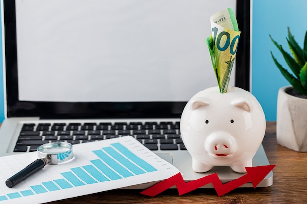 Hoge hoek van kantoorartikelen met spaarvarken en laptop
