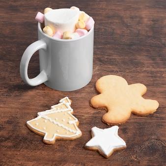 Hoge hoek van kerstmismok met koekjes en marshmallows