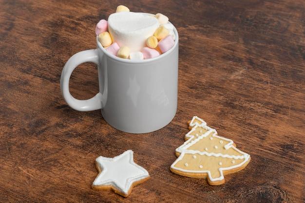 Hoge hoek van kerstmismok met marshmallows en koekjes