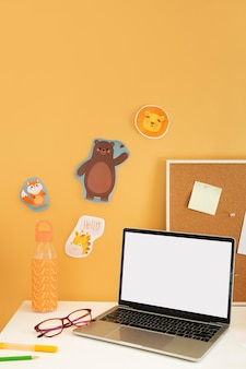 Hoge hoek van kinderbureau met laptop en teddybeer
