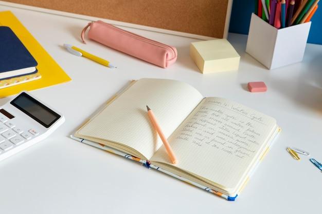 Hoge hoek van kinderbureau met notitieboekje