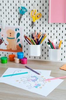 Hoge hoek van kinderbureau met tekeningen en potloden