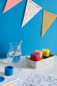 Hoge hoek van kinderbureau met verf en tekening