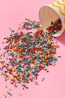 Hoge hoek van kleurrijke beker morsen van hagelslag