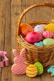 Hoge hoek van kleurrijke paaseieren in mand met konijntje