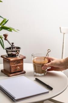 Hoge hoek van koffieglas met grinder en notitieboekje op tafel