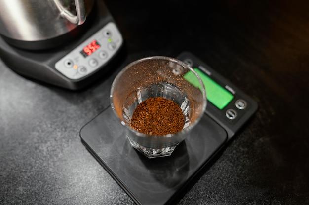 Hoge hoek van koffieglas op schaal met ketel